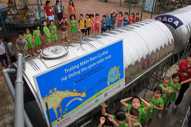 children gathered around large metal water tanks