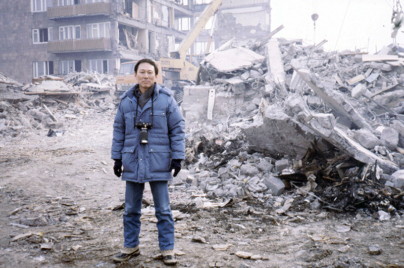 Lew standing in front of rubble from a building