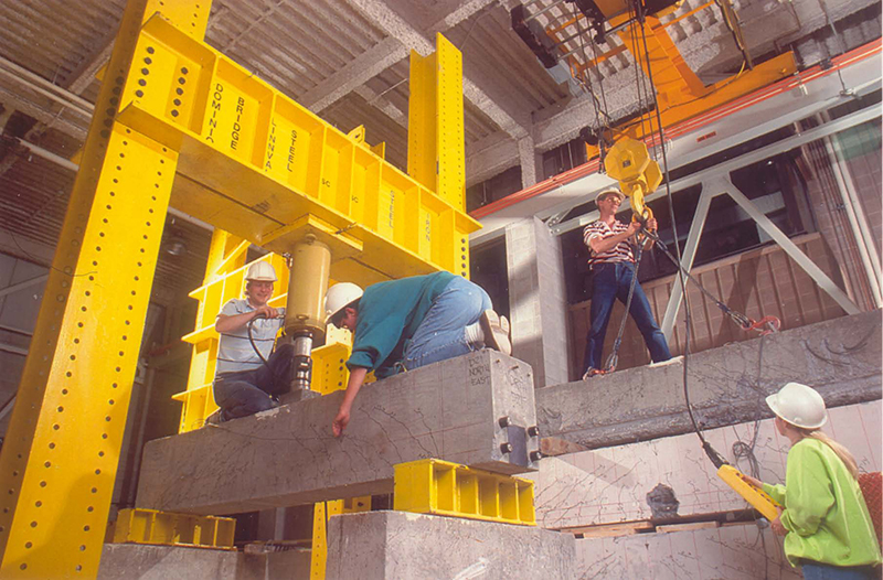 workers on concrete and steel beams inside warehouse