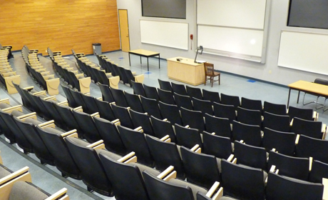 empty classroom with rows of seats and white boards at front
