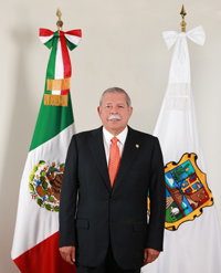 photo of Egidio Torre-Cantu standing in front of flags